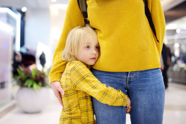 Little boy embrased his mother. Shyness, fears, anxiety. stock photo