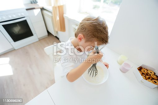 488109116 istock photo little boy enjoy cooking in kitchen interior 1130696090