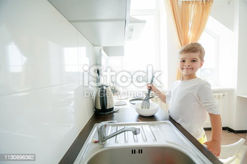 488109116 istock photo little boy enjoy cooking in kitchen interior 1130696362
