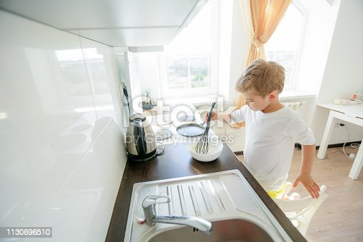 488109116 istock photo little boy enjoy cooking in kitchen interior 1130696510