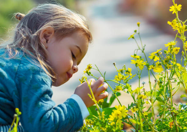 Kleiner Junge genießt Blumenaroma – Foto