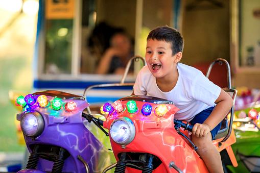 Little boy enjoying his ride at carousel in amusement park