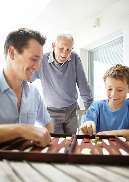 Little boy enjoys a game of backgammon with his father stock photo