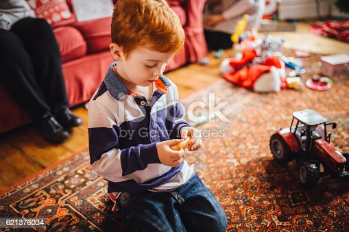 Little boy sat on the living room floor on Christmas morning holding some tangerine in-between his fingers. Part of an elderly woman is sitting on the sofa. Christmas paper and  toys can be seen scattered on the floor in the background.