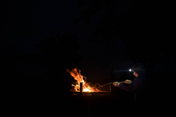 Little boy enjoys playing by the camp fire stock photo