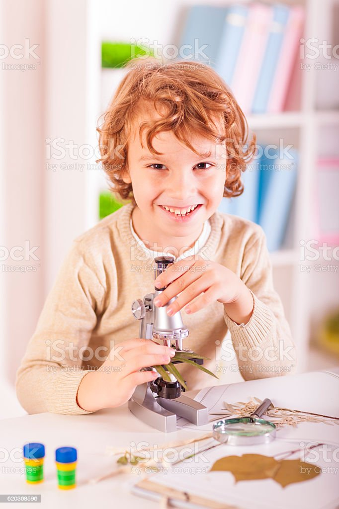 Little boy examing plants specimen with his microscope zbiór zdjęć royalty-free