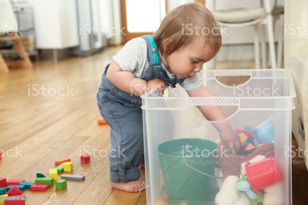 Little boy standing by plastic box with toys and looking in it\'s...