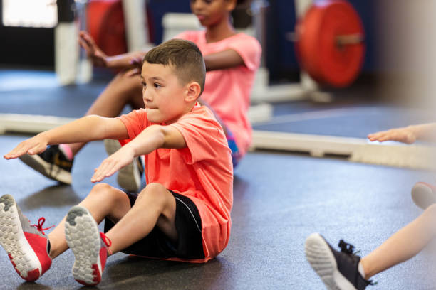 Little boy exercises during PE class Elementary schoolboy concentrates while performing a sit up during fitness class or PE class. touching toes stock pictures, royalty-free photos & images