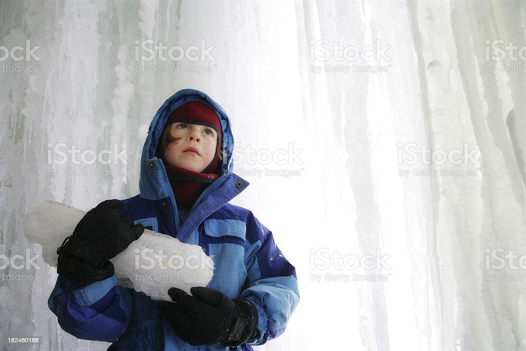 Menino explora atrás de uma cachoeira congelada foto royalty-free