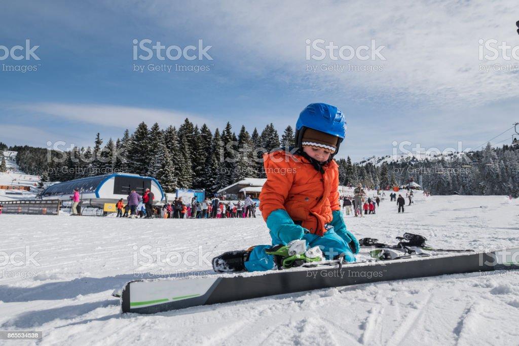 little boy exploring ski equipment stock photo