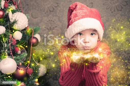 istock Little boy fairy blowing fairy magical glitter, stardust at Christmas 498856908