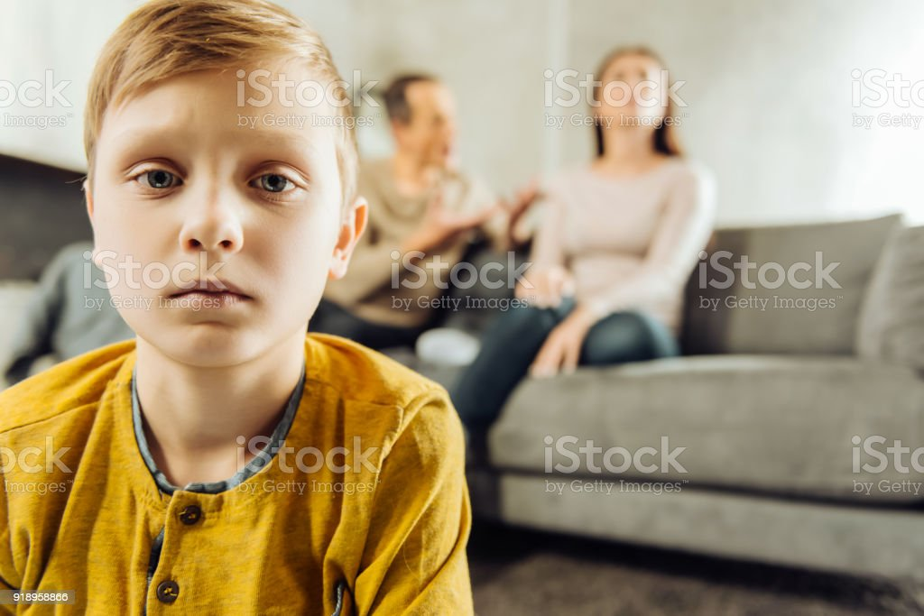 Little boy feeling lonely while his parents quarrelling stock photo