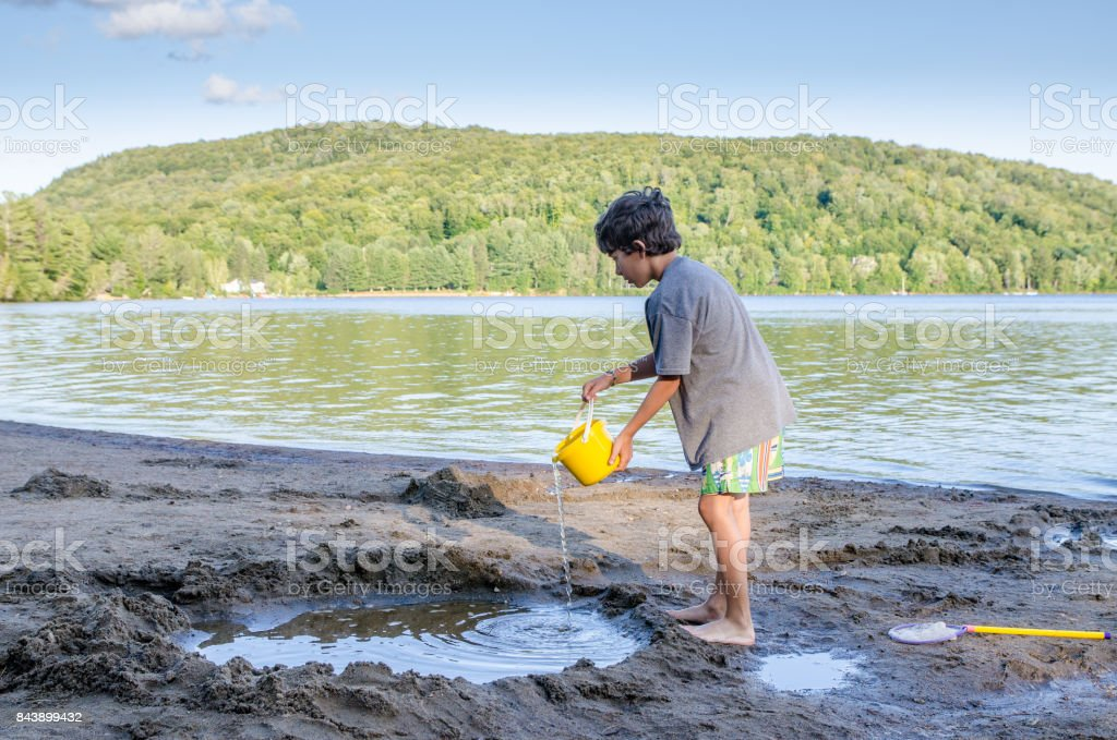 Little boy filling sand hole with water on beach besides the lake during summer vacations day stock photo
