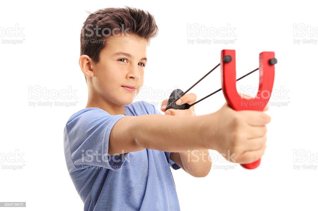 Little boy firing a rock from a slingshot stock photo