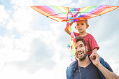 Father and son having fun, playing with kite together.