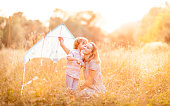Cute little boy flying a kite with his mother on a playing field. Bright sun in the background.