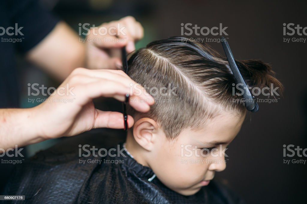 Little Boy Getting Haircut By Barber While Sitting In Chair At Barbershop. - 免版稅人圖庫照片