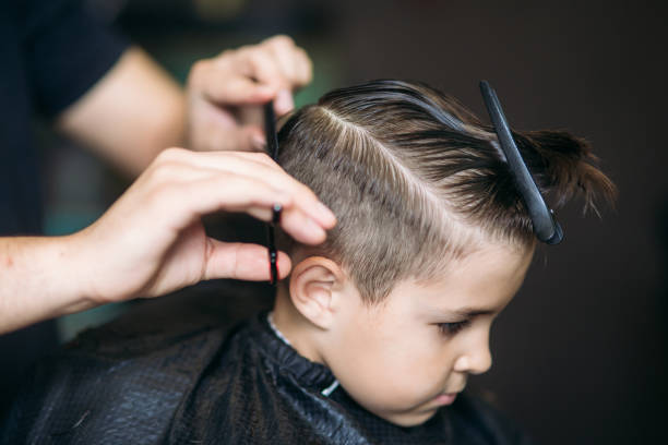 little boy getting haircut by barber while sitting in chair at barbershop. - peinado fotografías e imágenes de stock
