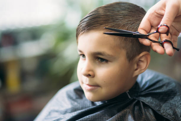 Little Boy Getting Haircut By Barber While Sitting In Chair At Barbershop Stock Photo