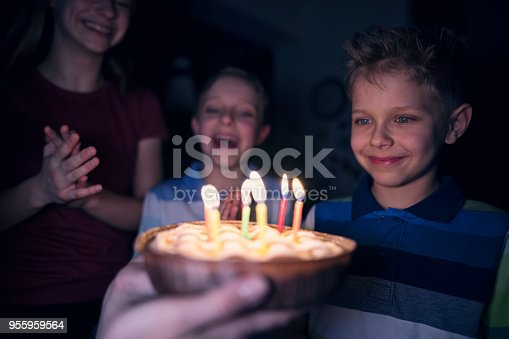 Little boy aged 7 getting his birthday cake. Two other kids are cheering and clapping.