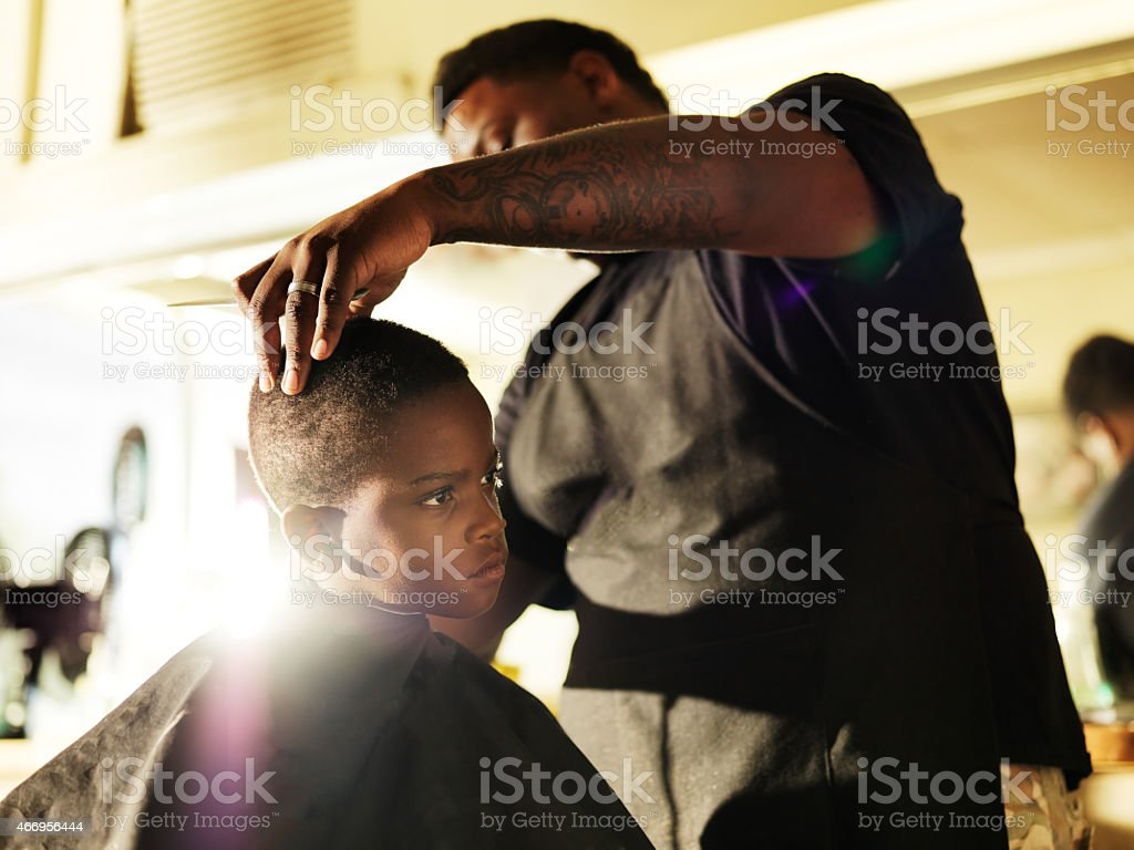 little boy getting his hair cut in barber shop stock photo