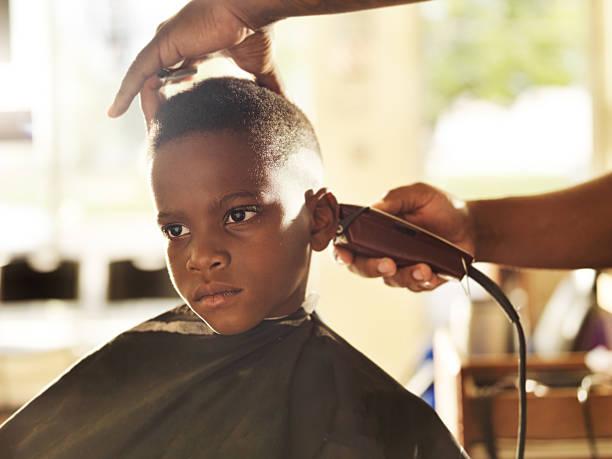 little boy getting his head shaved by barber stock photo