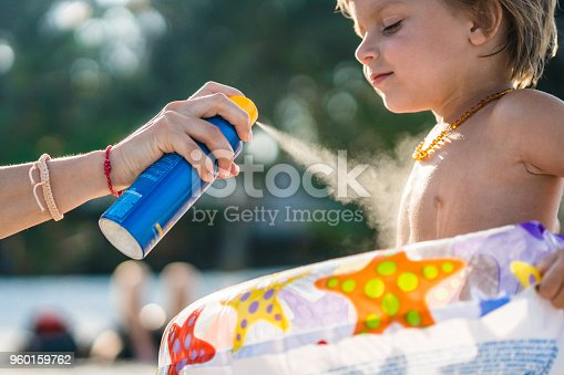 Unrecognizable mother spraying suntan lotion on her son's body at the beach.