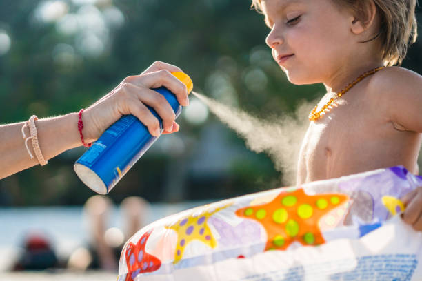 Little boy getting sun protection from his parent on the beach. Unrecognizable mother spraying suntan lotion on her son's body at the beach. suntan lotion stock pictures, royalty-free photos & images