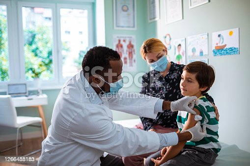 Close up of a pediatrician vaccinating his patient