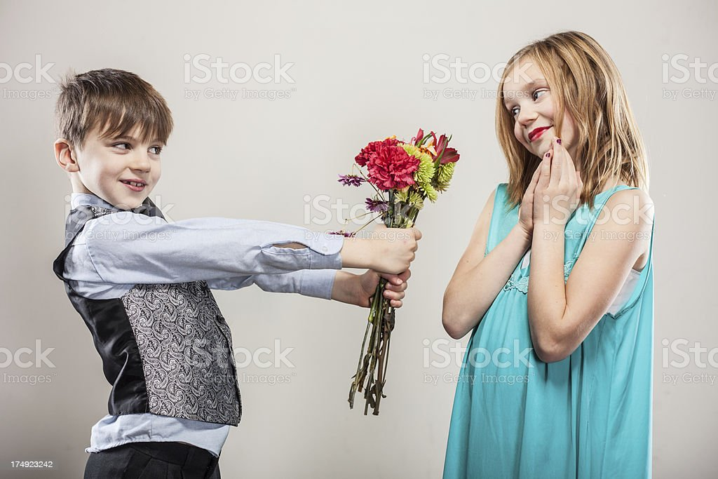 A sweet boy dressed up for a date giving a pretty girl a bouquet of...