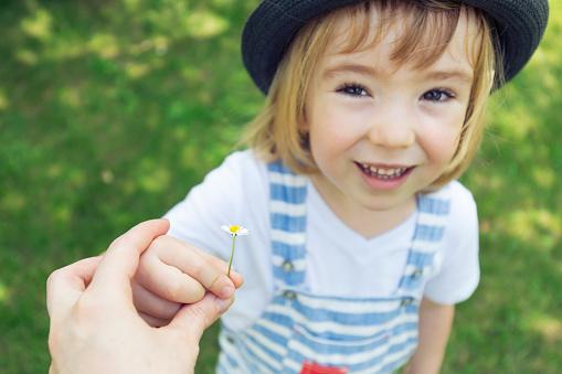 Cute little boy giving flower to mom