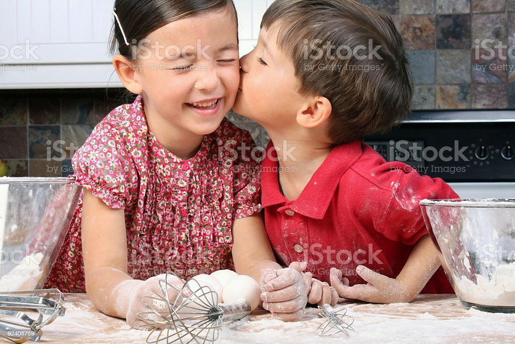 Little boy giving little smiling girl a kiss on the cheek royalty-free stock photo