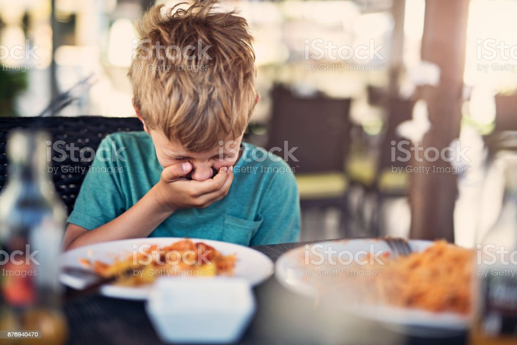 Little boy going to be sick in restaurant stock photo