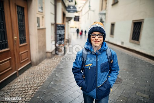 Little boys going to school on a cold autumn day. The boy is walking in the old town street of Brno, Czech republic. Nikon D850