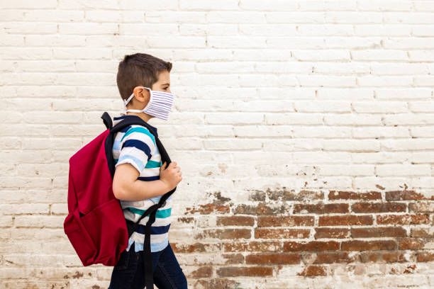 Little boy going to school with protective mask Little boy going to school with protective mask covid mask stock pictures, royalty-free photos & images