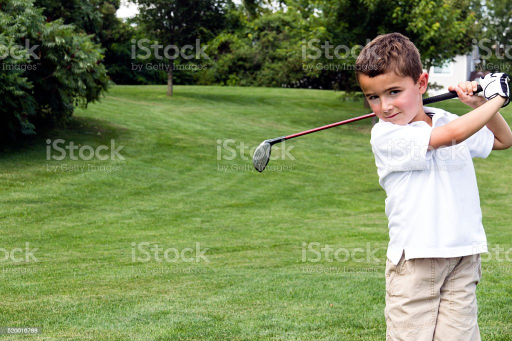 Little boy golfer swinging a club on the golf course stock photo