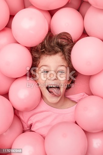 From above funny little kid showing tongue while having fun in heap of pink balloons during party