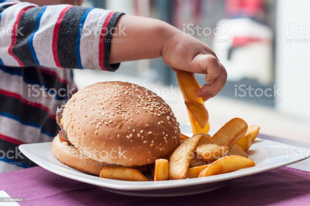 레스토랑에서 햄버거와 감자 튀김을 먹는 작은 아이 손 - 로열티 프리 감자 요리 스톡 사진