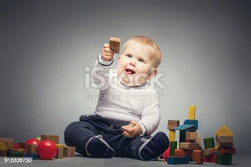 istock Little boy handing a wooden brick. 915338730