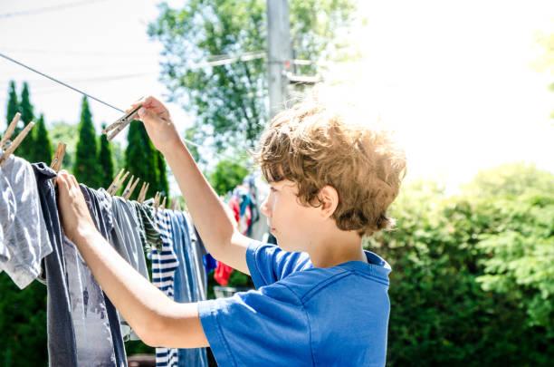 Kleiner Junge hängen Kleidung an Wäscheleine – Foto