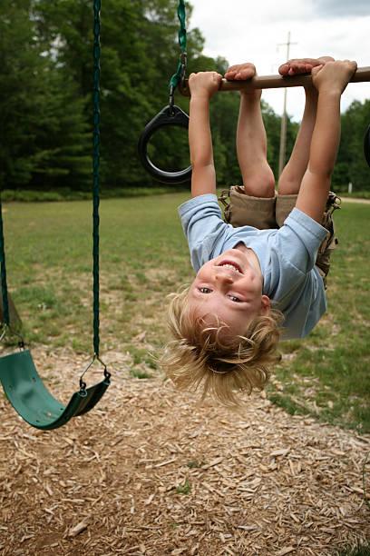 a little boy hanging upside down from a swing set - schommelen bungelen stockfoto's en -beelden
