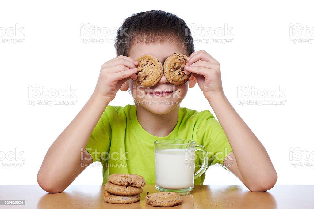 Little boy has breakfast cookies and milk isolated stock photo