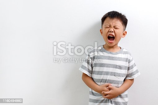Little Asian boy having abdominal pain, isolated on white background.