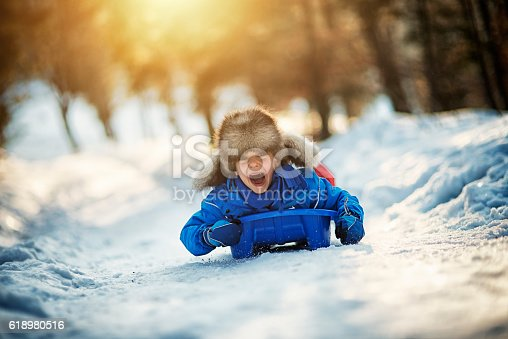 Little boy in funny fake fur hat sliding fast on his sled. The boy aged 6 is screaming with joy. Sunny winter day evening.