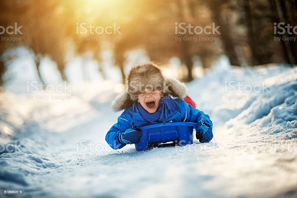 Little boy having extreme fun on his sled stock photo