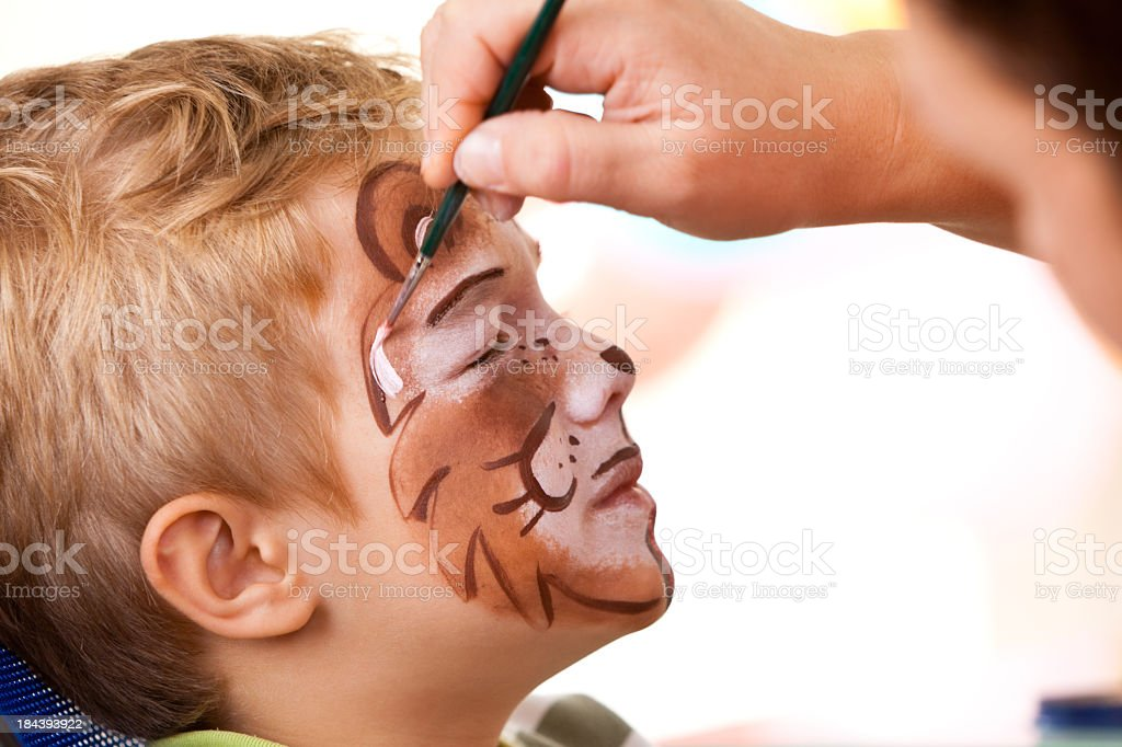 Little boy having face painted on birthday party royalty-free stock photo
