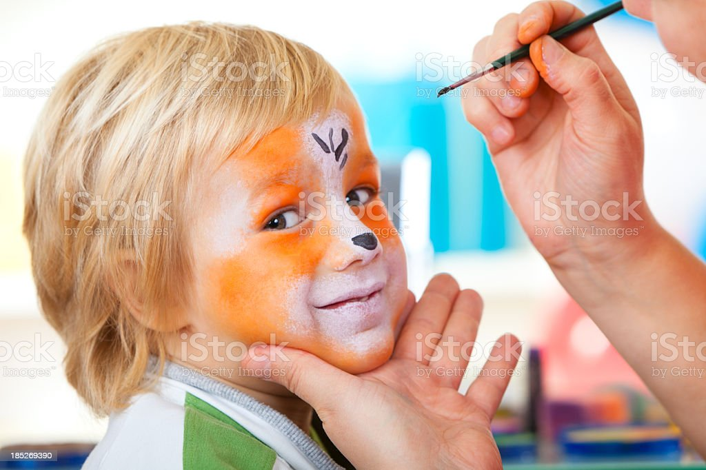 Little boy having face painted royalty-free stock photo