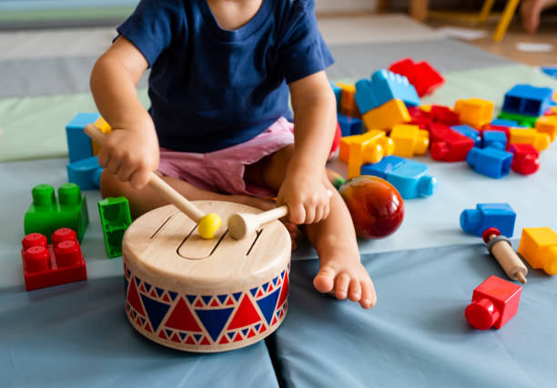 Little boy having fun and playing wooden toy drum stock photo