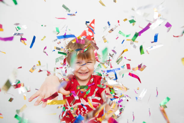 Little boy having fun celebrating birthday Little boy having fun celebrating birthday. Portrait of a child throws up multi-colored tinsel and confetti. Positive emotions. carnival children stock pictures, royalty-free photos & images