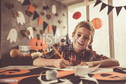 Copy space shot of cute little boy sitting at the table and having fun while drawing and making Halloween themed arts and crafts. He is smiling and looking at camera.